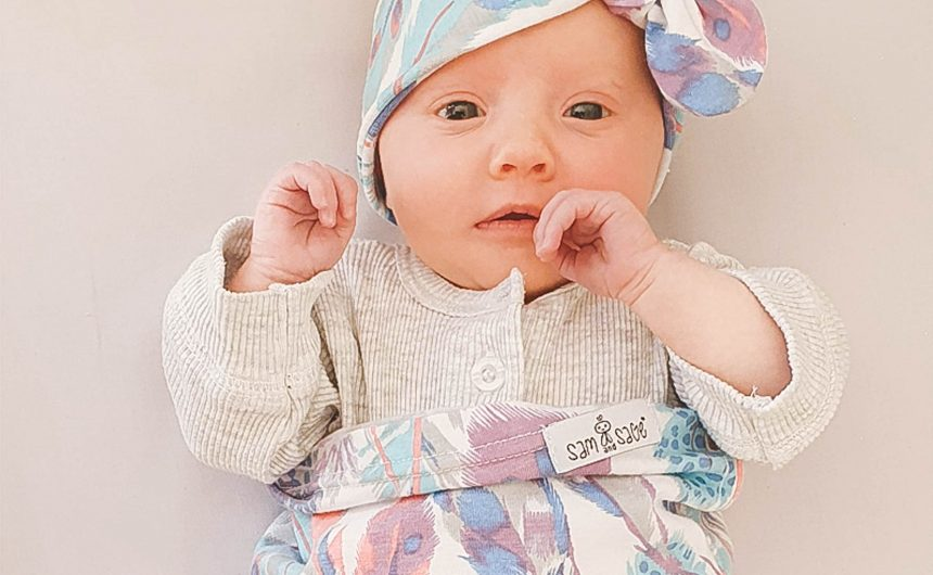 baby swaddled in feather swaddle sock with matching headband